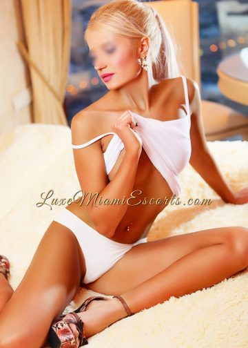 Alexa - hot Miami escort girl sitting on a bed in white panties and high heels