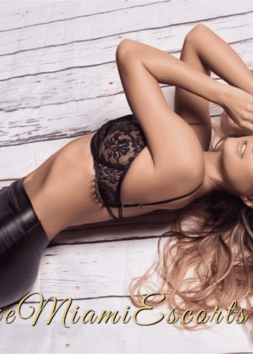 Luxe Miami Escort girl Bella laying down on the wooden deck in her sexy black leather pants and black bra