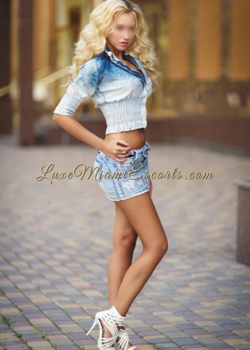 Gorgeous Miami blonde escort posing in her denim skirt and white heels