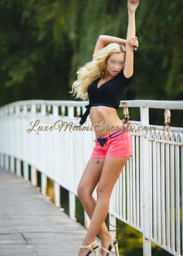 Luxe Miami escort girl Michelle posing in sexy high heels, pinks shorts and black top