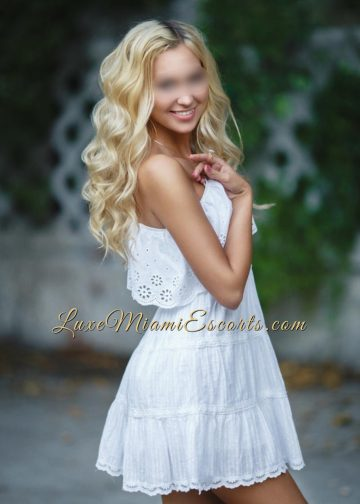 Beautiful Miami blonde escort posing in her white cotton dress