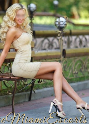 Miami blonde escort Michelle sitting on a bench in her super hot beige dress.