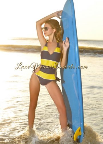 Glamorous Miami escort girl Renata posing with a surf board on a beach