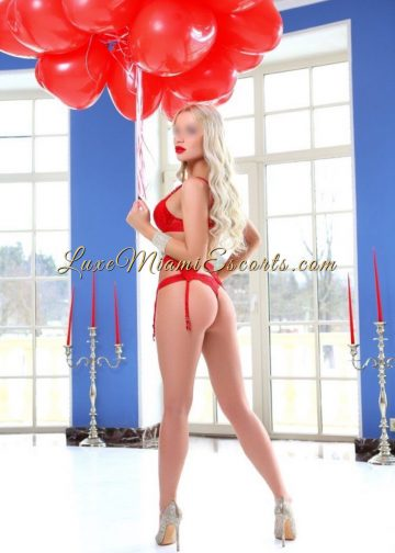 View from back of hot and sexy blonde Miami escort Anna posing with red balloons in her red lingerie and silver pumps