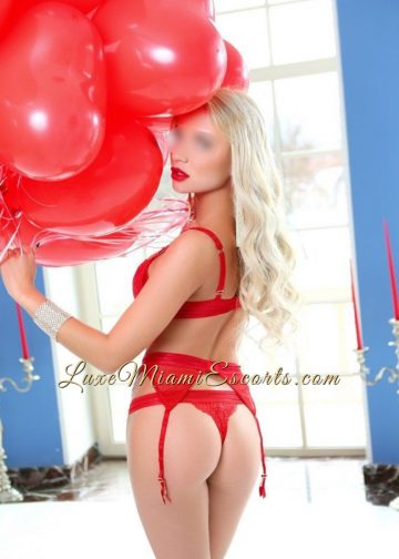 Stunning long hair blonde Miami escort model Anna showing her nice butt while wearing red lingerie and holding red balloons