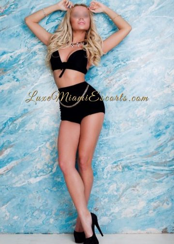 Luxe Miami escort model Anna posing in her black lingerie and black high heels on a light blue stone background