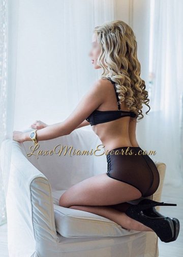 Hot and sexy long hair blonde escort model Anna standing on her knees on the armchair in her black lingerie, wearing high heels