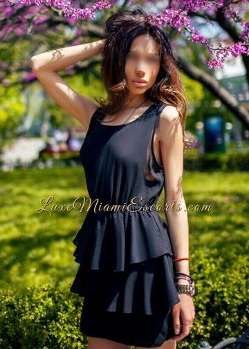 Ava - brunette Miami escort model posing in her short black dress