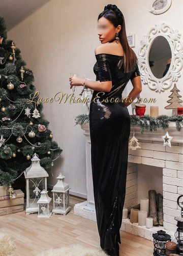 Beautiful Miami escort Ava in her long black evening dress, standing next to decorative fireplace and Christmas tree