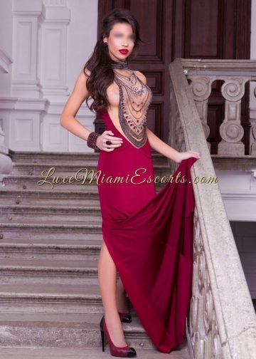 High class Miami escort Camila standing on a stairs in her long burgundy evening dress and black and burgundy high heels