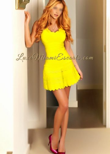 High class tall and busty Miami escort model Carmen in her sexy yellow dress and purple high heels