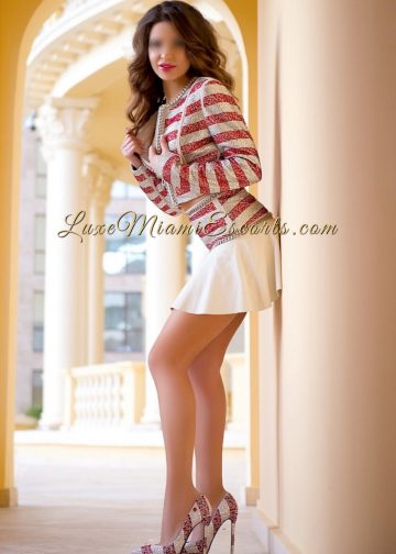 Miami escorts model Carolina posing on her stripy pink and silver blouse, matching high heels and white skirt
