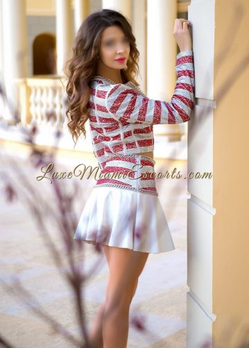 Side view of high class Miami escort model Carolina, dressed in short white and pink skirt and matching top