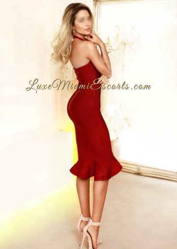 Hot, slender Miami blonde escort Diana posing in her red evening dress and sexy beige high heels