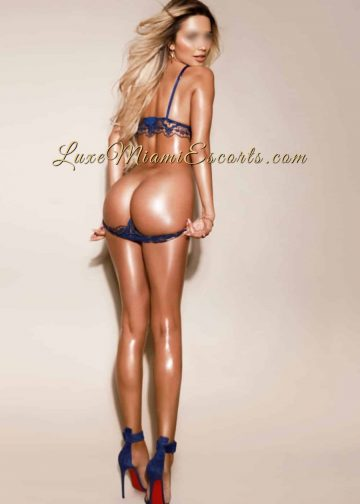 Miami blonde escort Diana showing her butt, while wearing sexy blue lingerie and blue high heels