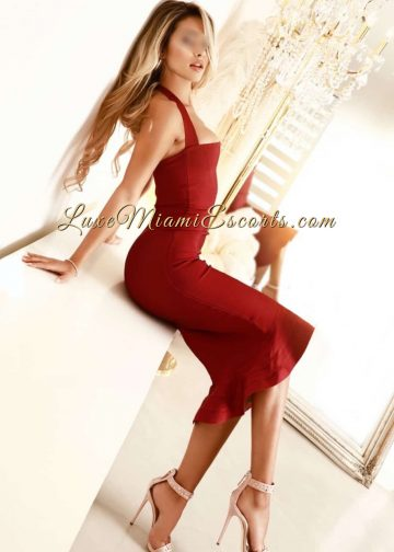 Hot blonde escort girl posing in her red cocktail dress and beige high heels in Miami