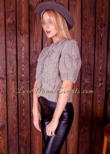 Miami blonde escort Emma in her leather pants, sweater and a hat