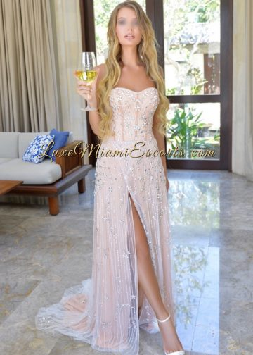 Top quality Miami blonde escort Eva posing in her gorgeous cocktail dress with a glass of white wine inside of luxury house