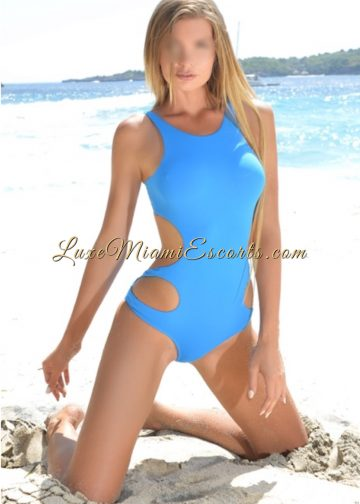 Stunning supermodel and elite escort in Miami posing on a beach in her light blue swim suit