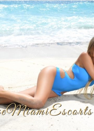 Horizontal photo of Miami super model escort Eva, laying on a beach in her sexy light blue swimwear