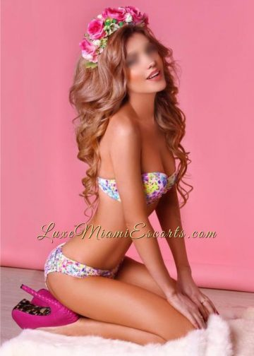 Miami escorts model Isabella posing in her sexy swim suite and purple high heels on a pink background