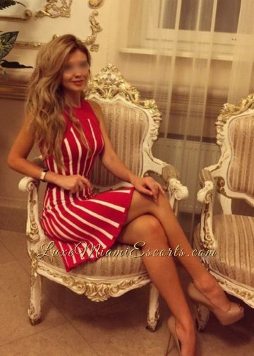High class Miami escort Isabella sitting on a luxury chair in her stripy red and white dress