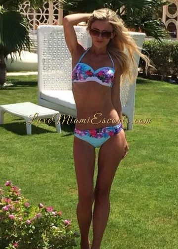 Slim and sexy Miami blonde escort Isabella standing in her colorful swim wear