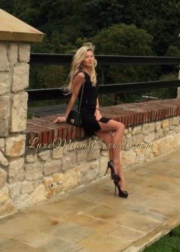 Amateur pic of professional blonde escort model, posing in her black dress