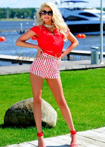 Miami escort model Jessica posing in her sexy red blouse, stripy red and white shorts and red high heels.