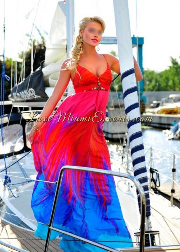 Beautiful blonde escort girl posing on a yacht in Miami, wearing her long red and blue dress