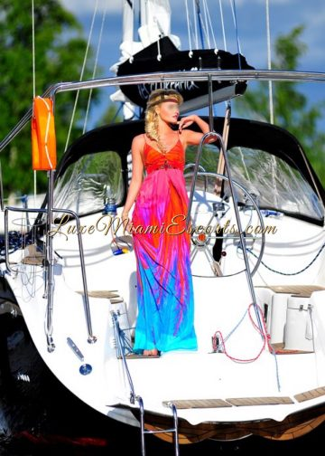 Jessica posing on a yacht in Miami, wearing long red and blue dress. An amazing Miami escorts model