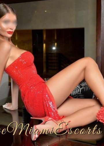 Horizontal photo of super hot dirty blonde Miami escort model Juliet posing in her red evening dress