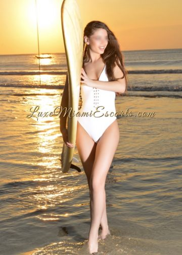 Gorgeous brunette Miami escort posing on a beach with a surf board, wearing her white swimsuit