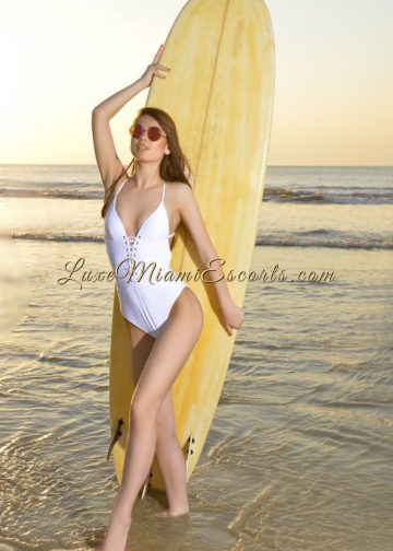 Beautiful Miami brunette escort model Katie posing on a beach with a surfboard, wearing white swimsuit and sunglasses