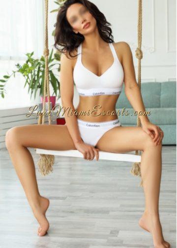 Hot Miami brunette escort sitting bear foot, wearing white Kelvin Klein panties and bra
