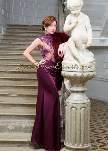 Lorena - petite brunette with short hair posing in her burgundy long evening dress. Presented by LUXE Miami Escorts
