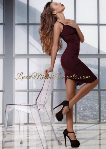 Gorgeous Miami brunette escort in burgundy dress and super high black heels, view from the side