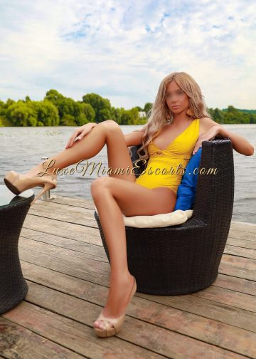 Beautiful high end blonde escort model Monica showing her gorgeous legs, wearing beige high heels and yellow swimwear
