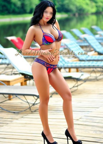 Luxury escort model Natally posing by the pool in Miami in her sexy red and blue lingerie and black high heels
