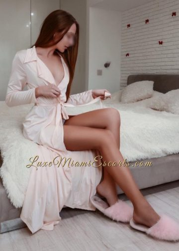 Sexi Miami escort Nicole sitting on a bed in her pink robe and pink slippers, showing her gorgeous legs