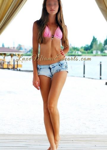 Gorgeous Miami escort Nicole posing out of cabana in her sexy denim shorts and pink bra