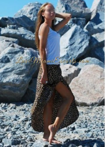 Miami escort model Nicole standing next to the rocks in her leopard skirt and white top