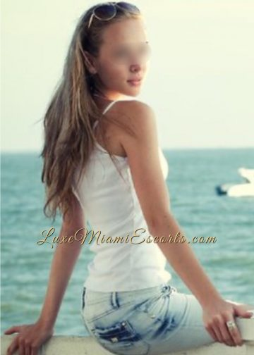 Hot Miami escort girl Nicole at the beach, sitting on a fence in her sexy jeans and white top