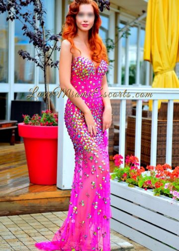 Miami redhead escort Olivia posing in her long pink evening dress