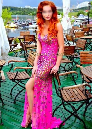 Hot redhead Miami escorts model Olivia posing at the waterfront restaurant in her pink evening dress