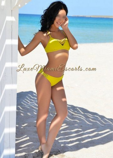 Escorts model Rebecca posing at the beach in her sexy yellow swim wear. Rebecca is an amazing escort model represented by LUXE Miami Escorts