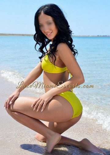 Gorgeous black hair brunette Miami escorts Rebecca standing on her knee on a beach in her sexy yellow swimwear