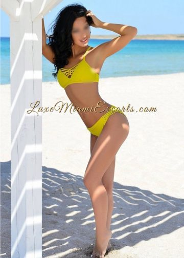 Gorgeous Miami brunette escorts model Rebecca posing on a beach in a yellow swim wear
