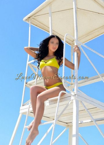 Sexy Rebecca - top rated Miami escort posing in her yellow swim wear at the beach tower