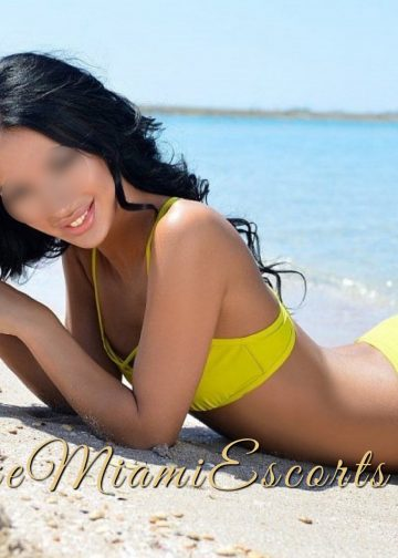 Miami escort Rebecca laying on a beach in her yellow swimwear